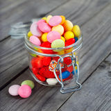Colorful candies in small jar Stock Images
