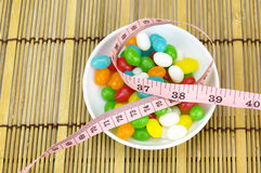 Colorful candies and tape measure. With shallow depth of field (dof)-diet and healthy teeth concept Stock Image