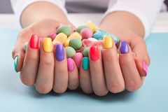 Colorful candies in womans hands. stock photos