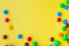 Colorful candies on yellow background royalty free stock photo