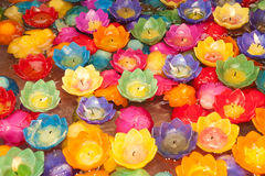 Colorful candle krathong floats in water. Stock Photography