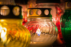 Colorful candles in the cemetery while All Saints' Day.  stock photos