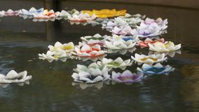 Colorful Candles in Lotus Shape Floating on Water in a Buddhist Temple. Pattaya. Thailand. Bowl of water in the temple, a big golden Buddha. Coins under water stock footage
