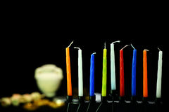 Colorful candles ready for hanukkah holiday. Eight candles are the symbol of the miracle happened on Hanukkah the Jewish holiday. In the background are oil pot stock images
