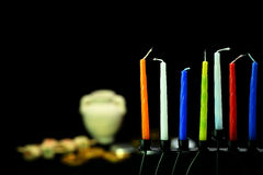 Colorful candles ready for hanukkah holiday. Eight candles are the symbol of the miracle happened on Hanukkah the Jewish holiday. In the background are oil pot royalty free stock images