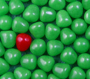 Colorful candy background. Lone red candy on background of green sweets or confectionery royalty free stock photo