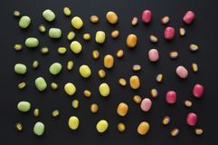 Colorful candy on black background. Green, yellow, orange and red candies stock image