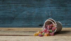 Colorful candy and blue bucket on wood background. A decorative pail of Christmas candy on wooden background royalty free stock photography