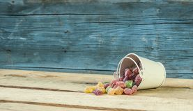 Colorful candy and blue bucket on wood background. A decorative pail of Christmas candy on wooden background royalty free stock photo