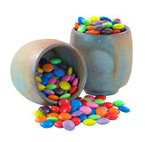 Colorful Candy Buttons. Colourful Chocolate Candy Buttons spilling from earthernware pots on white background Royalty Free Stock Photography