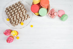 Colorful candy, cupcakes, macaroons, wafer rolls on white wooden background Royalty Free Stock Images