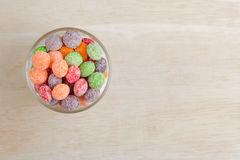 Colorful candy. In the glass cup on the wood block stock image
