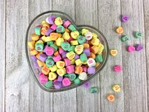 Candy hearts in a heart shaped bowl. Colorful candy hearts in a heart shaped glass bowl on a wood surface stock photos