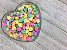 Candy hearts in a heart shaped bowl. Colorful candy hearts in a heart shaped glass bowl on a wood surface stock image