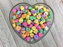 Candy hearts in a heart shaped bowl. Colorful candy hearts in a heart shaped glass bowl on a wood surface royalty free stock photography