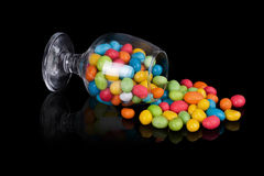 Colorful candy in inverted glass Stock Photos