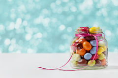 Colorful candy jar decorated with a bow against blue bokeh background Royalty Free Stock Image