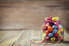 Colorful candy jar decorated with a bow against rustic wooden background Stock Photos