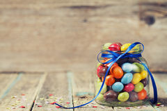 Colorful candy jar decorated with a bow against rustic wooden background Stock Image