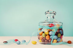 Colorful candy jar decorated with bow ribbon against blue background Stock Photo