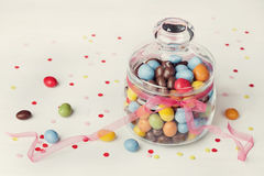 Colorful candy jar decorated with bow ribbon on white background with confetti Stock Photography