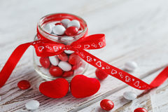 Colorful candy jar decorated with a red bow with hearts on white wooden background. Valentines day concept Royalty Free Stock Images