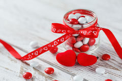 Colorful candy jar decorated with a red bow with hearts on white wooden background. Valentines day concept Royalty Free Stock Image