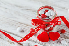 Colorful candy jar decorated with a red bow with hearts on white wooden background. Valentines day concept Stock Photo