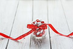 Colorful candy jar decorated with a red bow with hearts on white wooden background. Valentines day concept Stock Image
