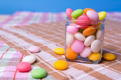 Colorful candy in jar on table with blue background Royalty Free Stock Photos