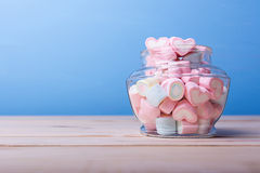 Colorful candy in jar on table with blue background. Colorful candy in jar on table royalty free stock photos