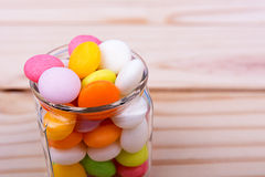 Colorful candy in jar on wooden table Stock Images
