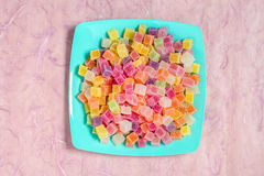 Colorful candy and jelly in color dish on pink background Royalty Free Stock Photo