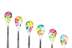 Colorful candy with  metal spoons Stock Images