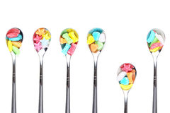 Colorful candy with  metal spoons Royalty Free Stock Images