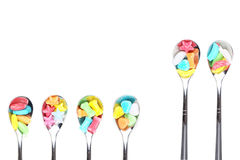 Colorful candy with  metal spoons Royalty Free Stock Photography