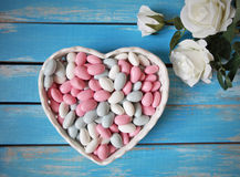 Colorful candy in white heart shaped bowl and white roses  on wooden table Stock Image