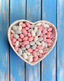 Colorful candy in white heart shaped bowl on wooden table stock photo