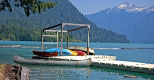Colorful Canoes on Dock of Mountain Lake. This summer scene shows colorful canoes at a dock at a beautiful mountain (Shuksan mountain) lake in Washington state Royalty Free Stock Image