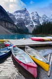 Colorful canoes docked at Moraine Lake stock images