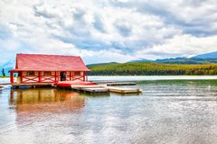 Maligne Lake in Jasper National Park in Alberta Canada. Colorful canoes lie on the boat house dock at Maligne Lake in Jasper National Park, Alberta, Canada. The Royalty Free Stock Photos