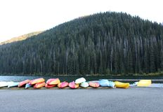 Colorful Canoes at Lightning Lake BC. Red, white, yellow and green canoes. and kayaks line the peaceful scenic shore of Lightning Lake in Manning Park BC Stock Photos