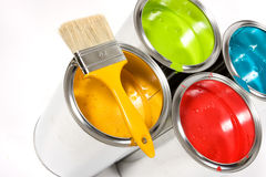 Colorful cans of paint. A background of colorful cans of paint with a brush resting on top stock image