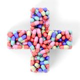 Colorful caplets in shape of medical cross Stock Photography