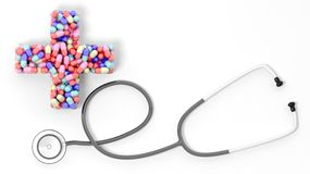 Colorful caplets in shape of medical cross and stethoscope Royalty Free Stock Image