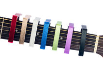 Colorful capo on guitar fingerboard, white background Royalty Free Stock Images