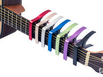 Colorful capo on guitar fingerboard, white background Royalty Free Stock Photos