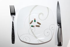 Colorful capsules and pills on plate with fork and knife on white background Stock Photo
