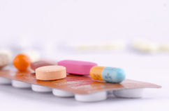 Colorful capsules and tablets on top a packed medication. Stock Image