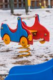 Colorful car swing on a playground in winter. Colorful car swing on a playground covered in snow in winter in Poland Stock Photos